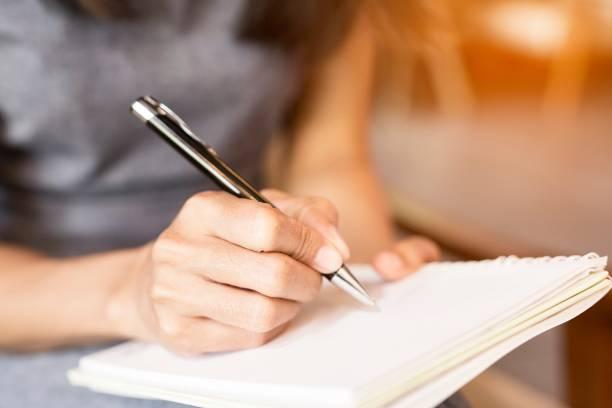 у женщин, держащих ручки, пишут тетрадь. концепция записи - писать стоковые фото и изображения