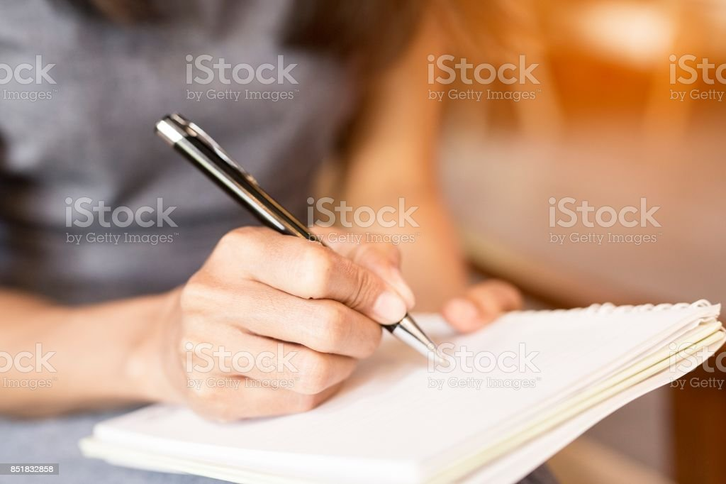 Women holding a pens writing a notebook. Recording concept stock photo