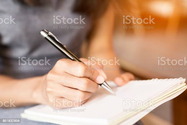 Women holding a pens writing a notebook. Recording concept