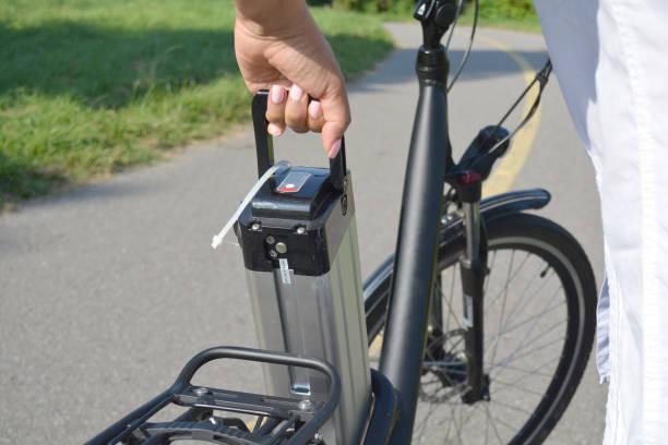 frauen halten akkus des elektro-fahrrad in der nähe von ihrem e-bike. weiblich e bike batterie herausnehmen. ökologie-konzept. laden von batterien. erneuerbare energien. - elektrorad stock-fotos und bilder
