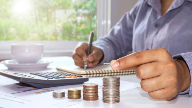 mujeres que poseen monedas y cartas de monedas apiladas, incluyendo cuadernos de trabajo de madera, ideas para ahorrar dinero y crecimiento financiero. - gerente de cuentas fotografías e imágenes de stock