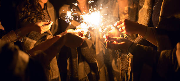 Women holding many sparklers in hands at night stock photo