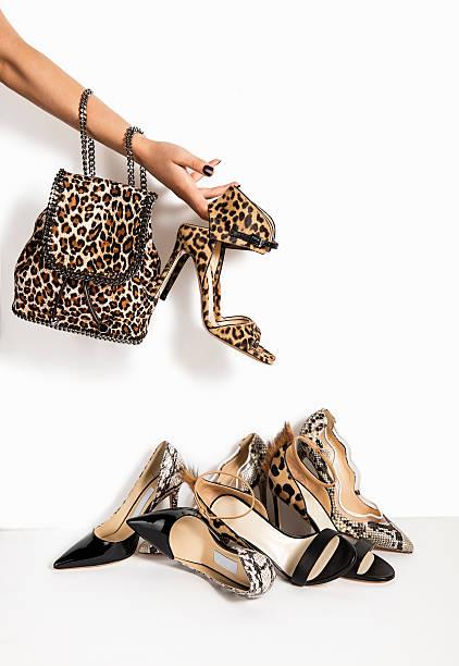 women holding shoes and handbag - neontasche stock-fotos und bilder