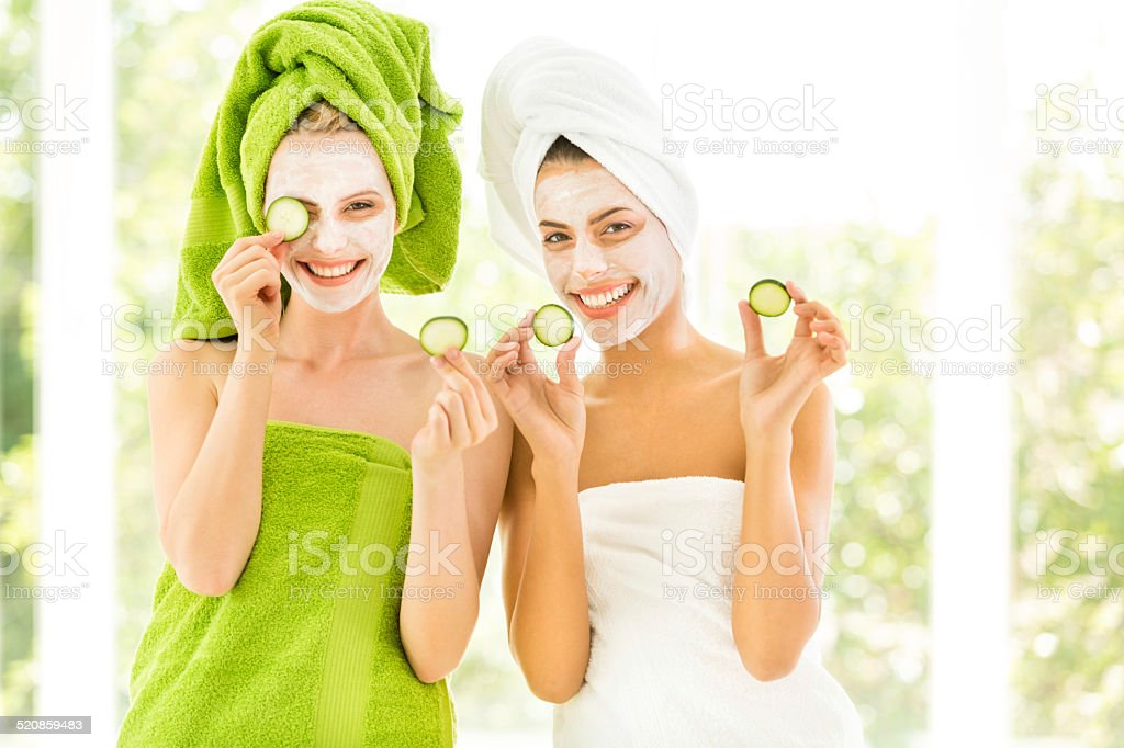 Women holding slices of cucumber stock photo