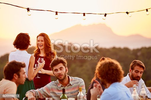 Happy women holding wine glasses while friends enjoying at dinner party