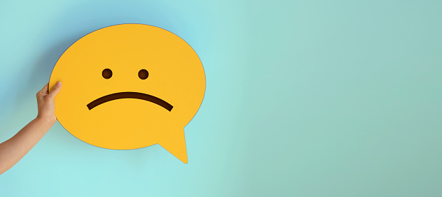 Women holding yellow speech bubble with sad face