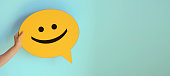 istock Women holding yellow speech bubble with smiley face 1250735834
