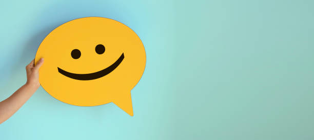 Women holding yellow speech bubble with smiley face stock photo