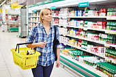 Women housewife with yellow basket shopping in supermarket