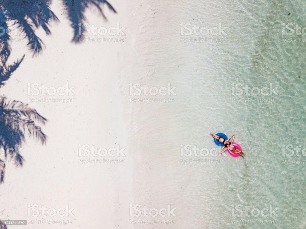 Women in a bikini enjoys the tropical sun Women in a bikini enjoys the tropical sun Above Stock Photo