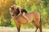 istock Women In A Black Dress Hugging Her Horse 819435872