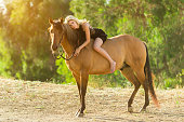 istock Women In A Black Dress Hugging Her Horse 819438248
