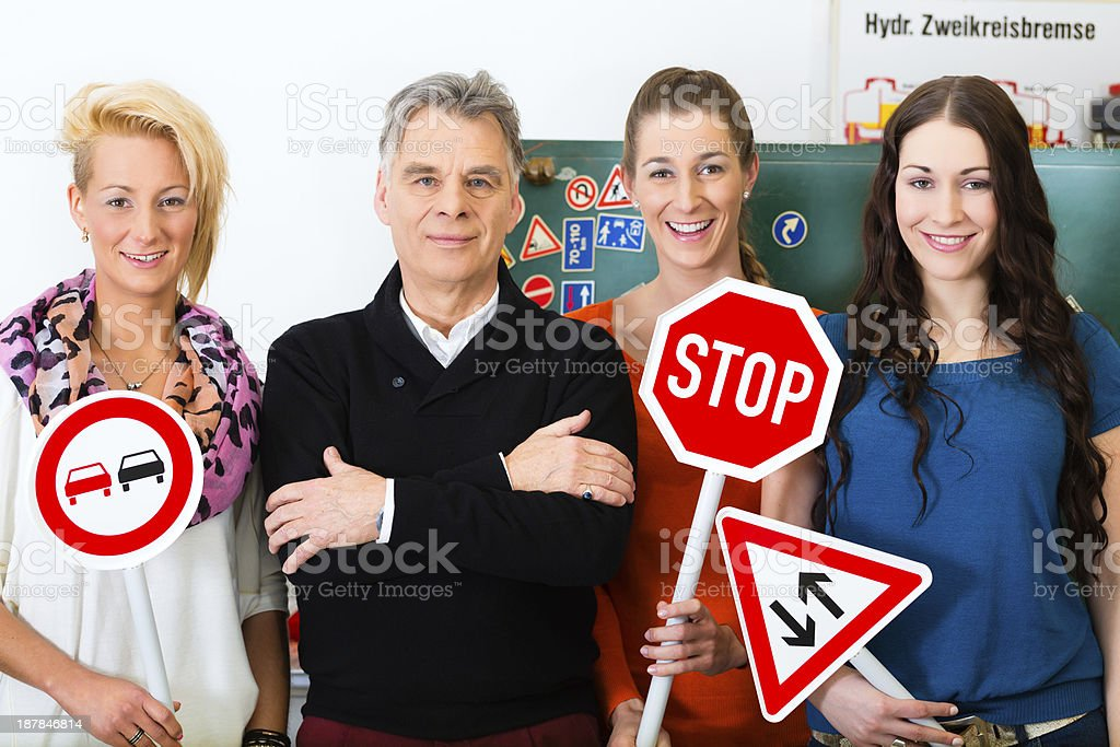 Women in a driving class holding signs with a male teacher stock photo