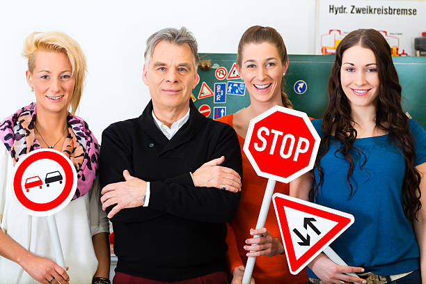 Women in a driving class holding signs with a male teacher Driving school - driving instructor and student drivers look at a tempo thirty Road sign, in the background are traffic signs driving instructor stock pictures, royalty-free photos & images