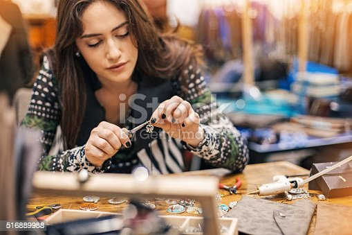 Young woman creating handmade jewelry in her studio