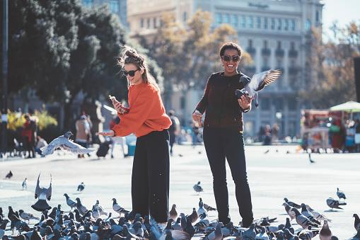 Women in Barcelona feeding pigeons