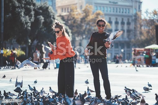 Two friends in Barcelona having fun with the pigeons