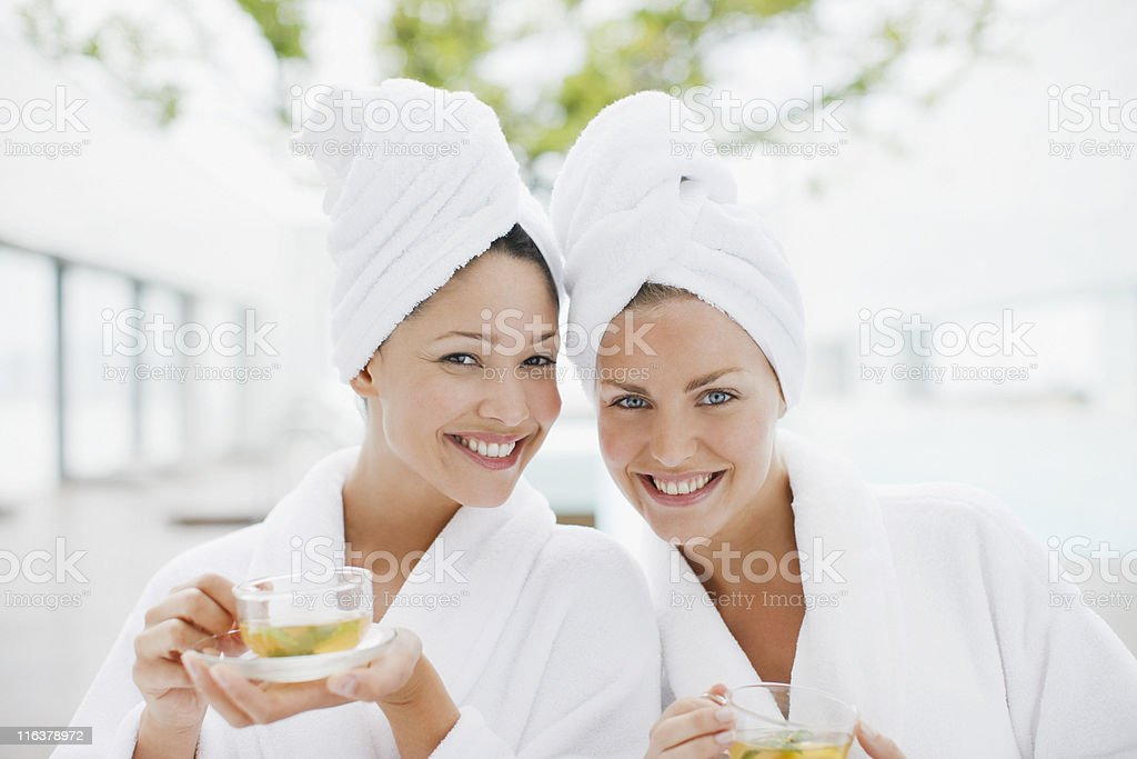 Women in bathrobes drinking tea at spa stock photo