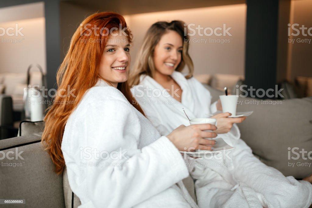 Women in bathrobes enjoying tea and wellness weekend stock photo