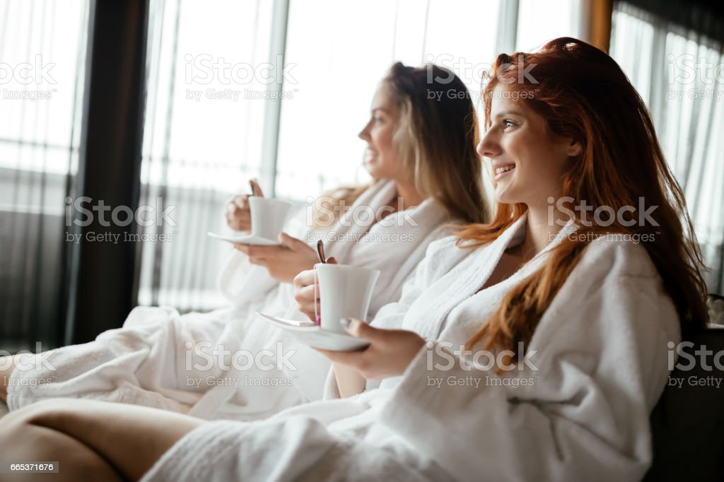 Women in bathrobes enjoying tea and wellness weekend stock photo