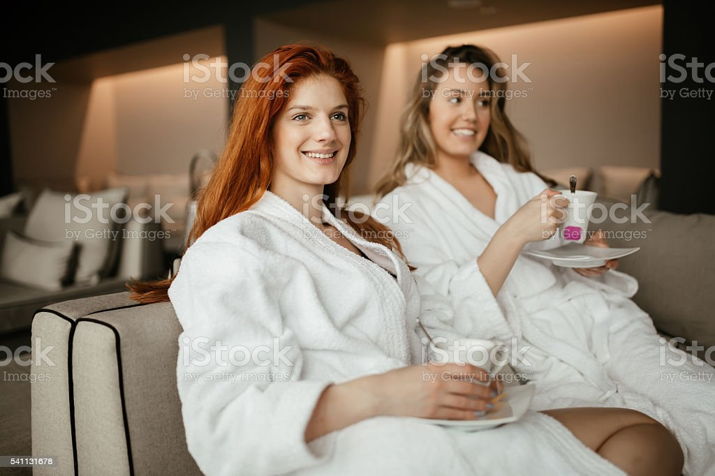 Women in bathrobes enjoying tea stock photo