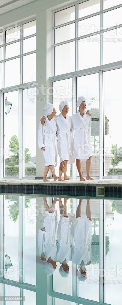 Women in bathrobes talking on bench poolside at spa royalty-free stock photo