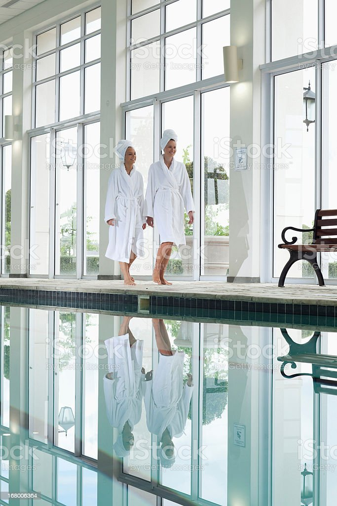 Women in bathrobes walking along swimming pool at spa royalty-free stock photo