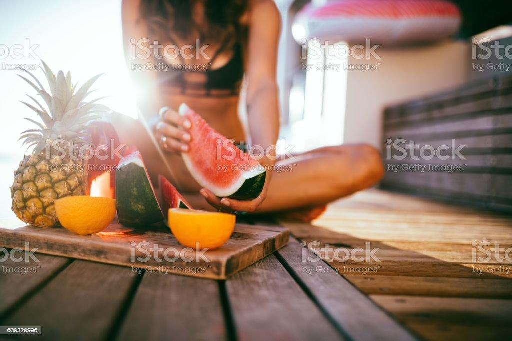 women in bikini enjoying fresh fruit platter at the pool stock photo