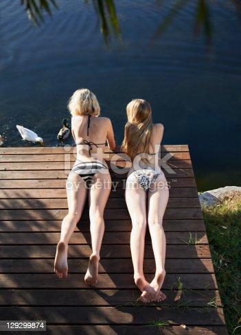 istock Women in bikinis laying on deck 129299874