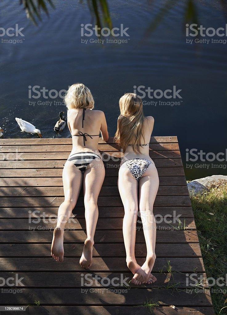 Women in bikinis laying on deck stock photo