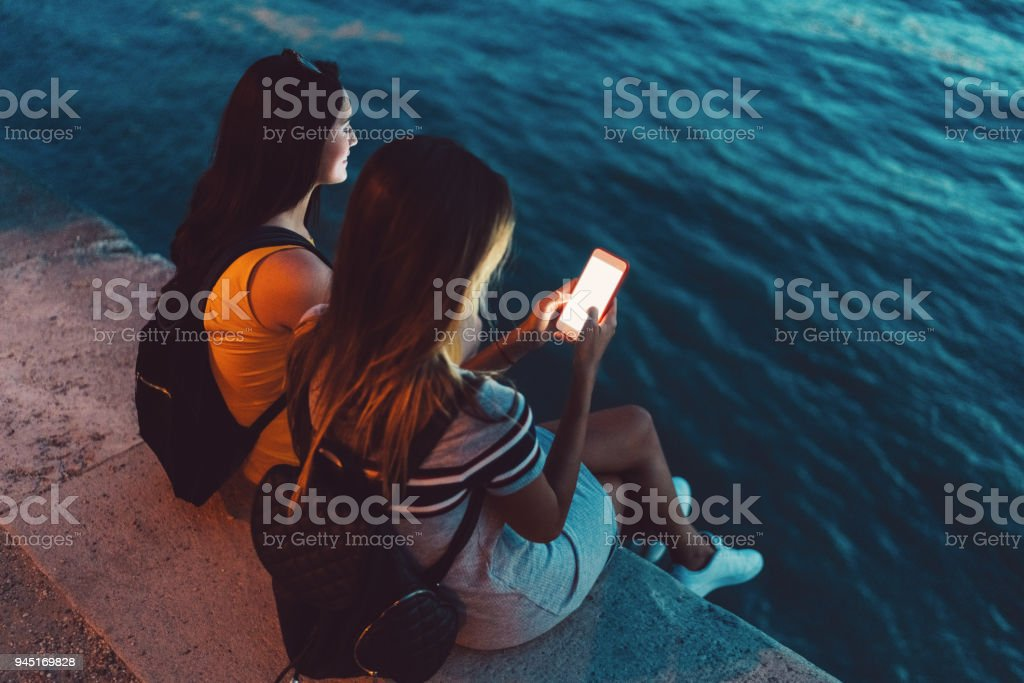 Women in Budapest texting at Danube riverbank stock photo
