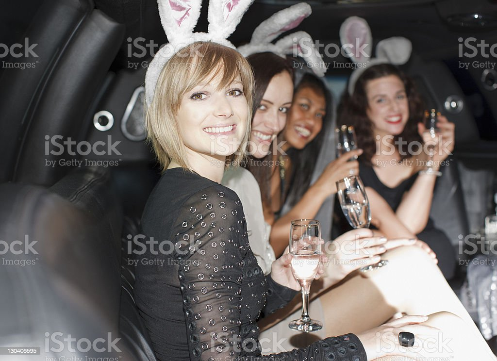 Women in bunny ears having champagne in back of limo stock photo