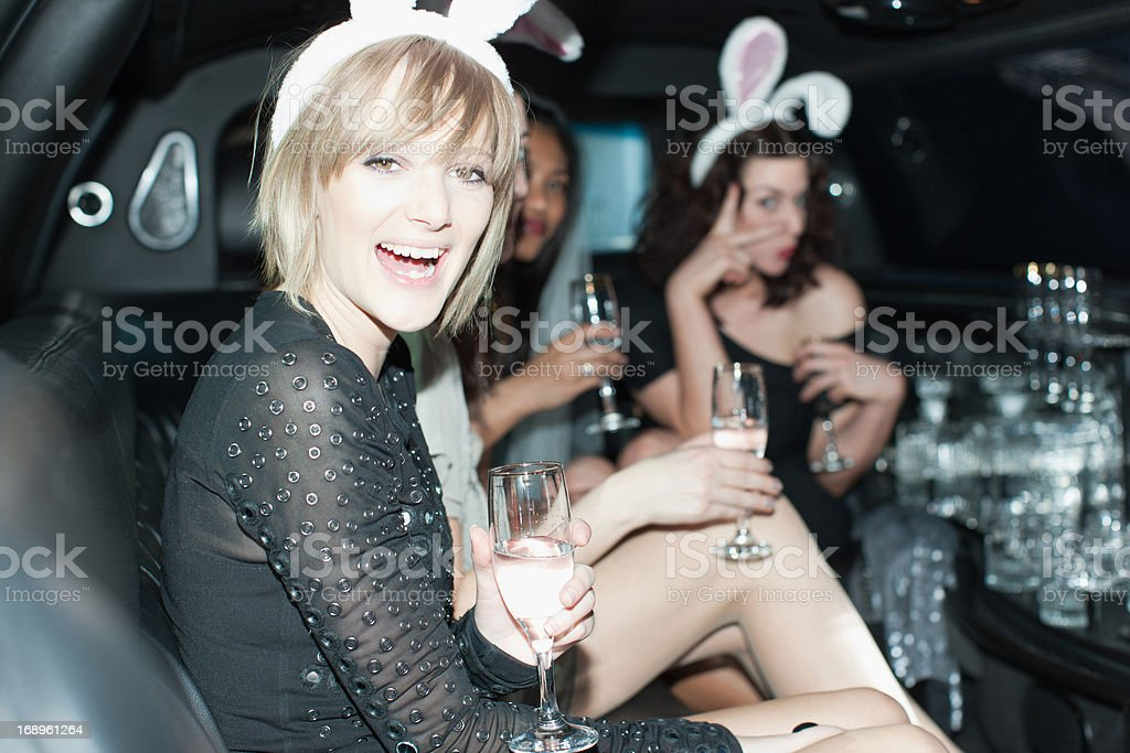Women in bunny ears having champagne in back of limo royalty-free stock photo