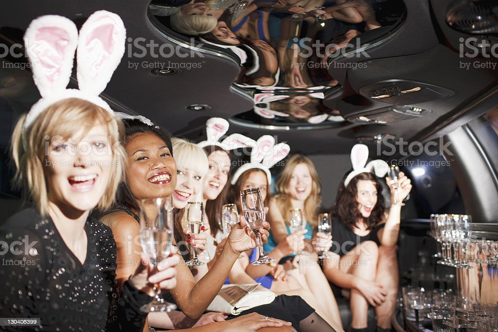 Women in bunny ears toasting in back of limo royalty-free stock photo