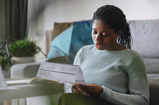 Portrait of a young African American businesswoman reading a utility bill while working remotely from home.