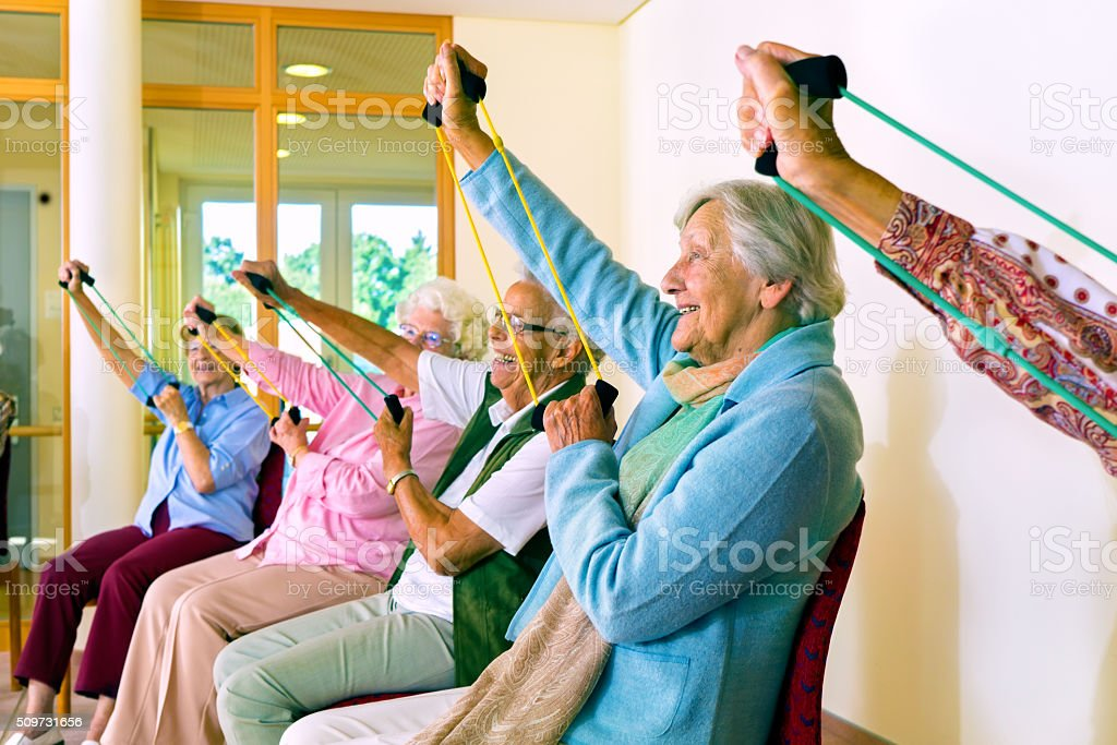 Women in chairs using stretching bands. stock photo