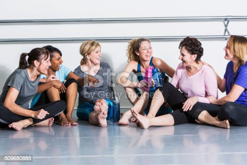 istock Women in exercise class, taking break 509680885