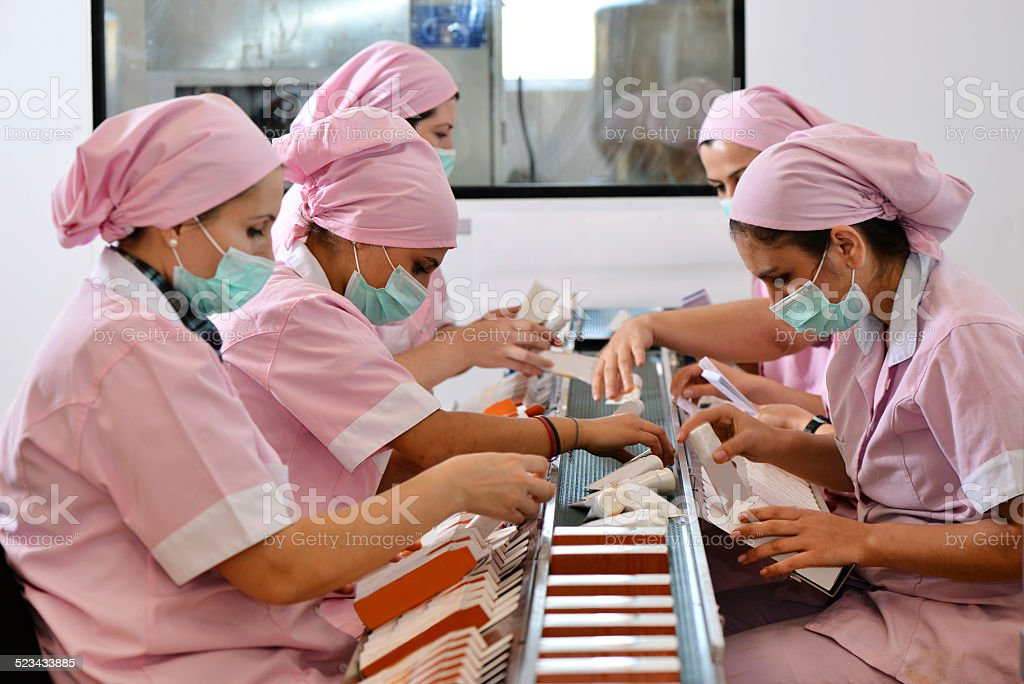 Women in factory are packing body care products stock photo