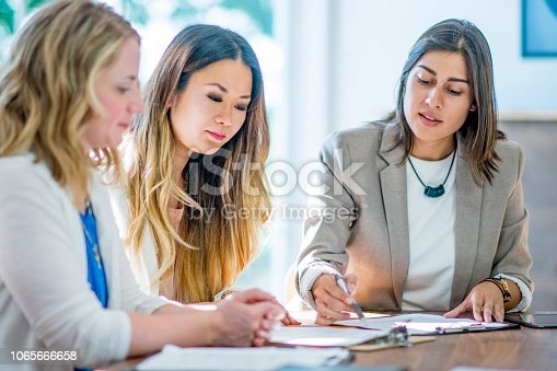 Three women sitting at a table in a business meeting. They are looking at papers and notepads on the table. The women are in professional attire.