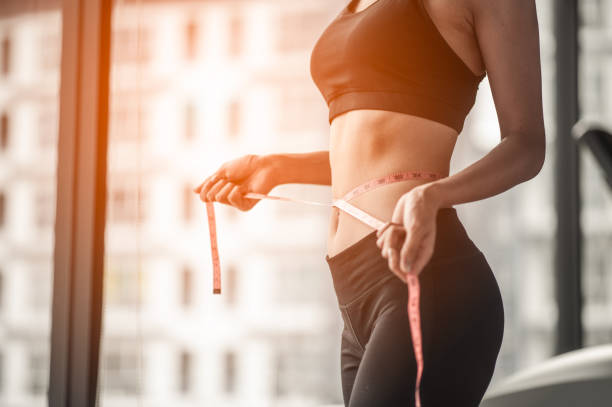 women in fitness uniform And it is using the waist line in gym. women in fitness uniform And it is using the waist line in gym. liposuction stock pictures, royalty-free photos & images