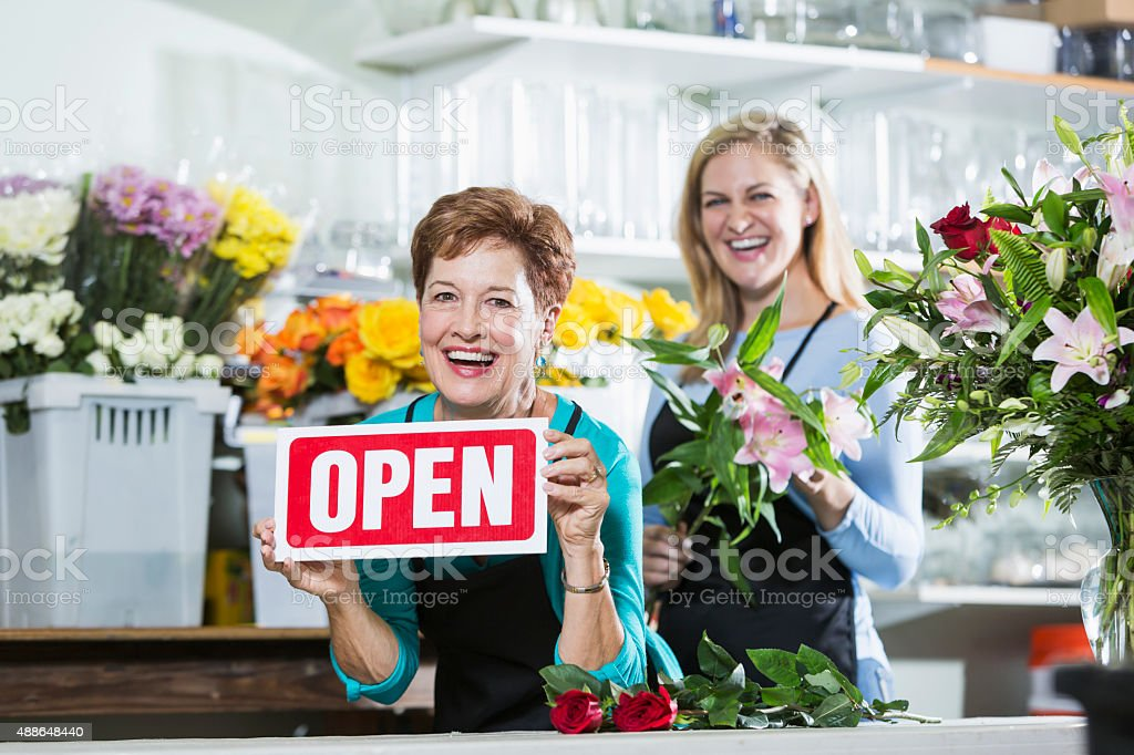 Flower shop open for business. A mature woman in her 60s working as a...