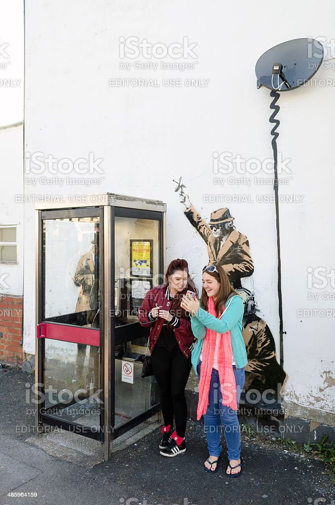 Women in front of a possible Banksy artwork, Cheltenham stock photo
