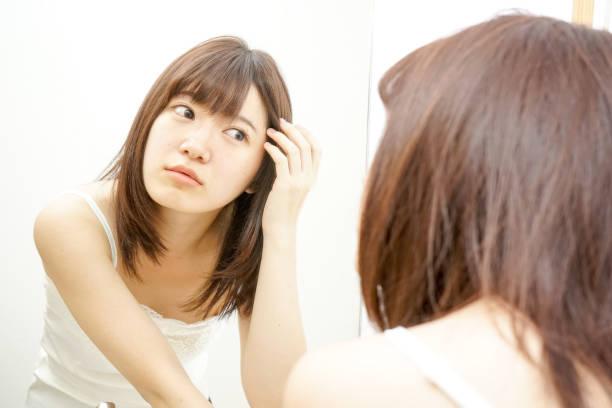 鏡の前にいる女性 - 人の髪 ストックフォトと画像