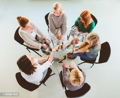 956725746 istock photo Women in group discussion during therapy session 1183961942