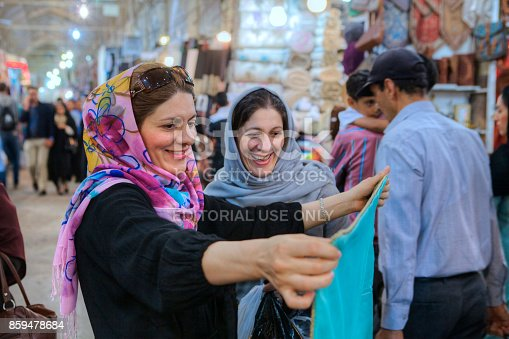 Fars Province, Shiraz: Two smiling Muslim women in colored hijab choose fabric to buy at the Vakil Grand Bazaar.