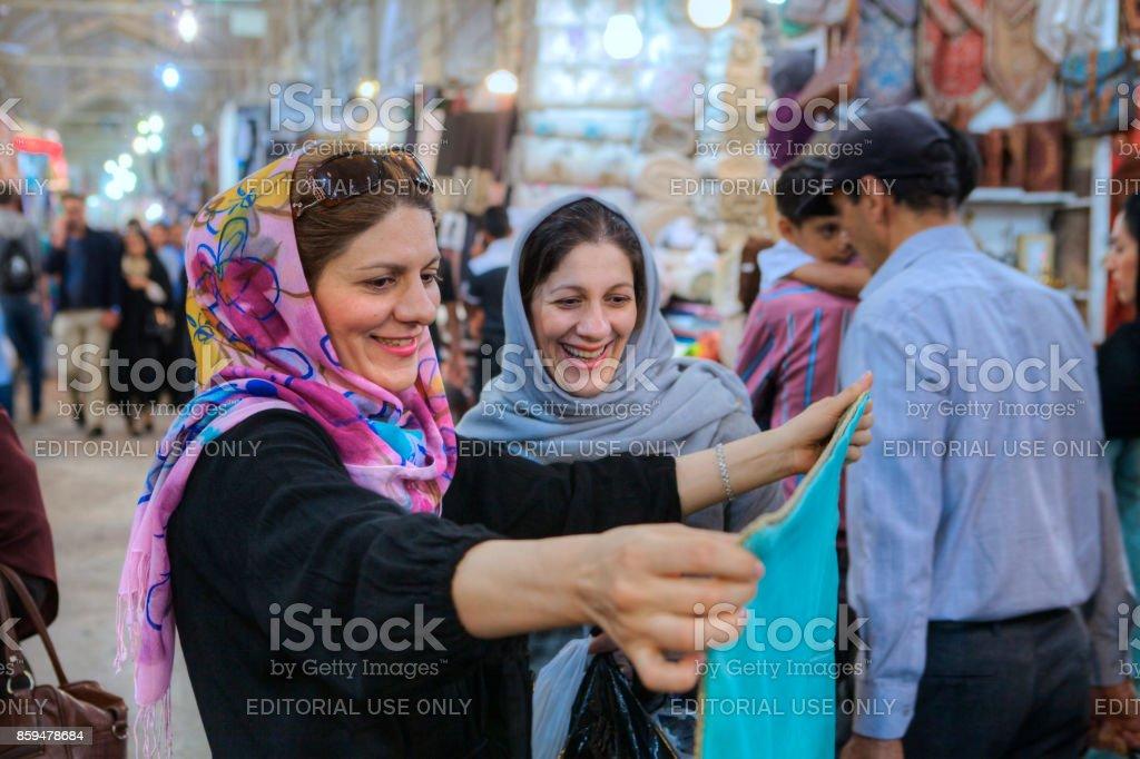 Women in hijab choose fabric in city market, Shiraz, Iran. stock photo