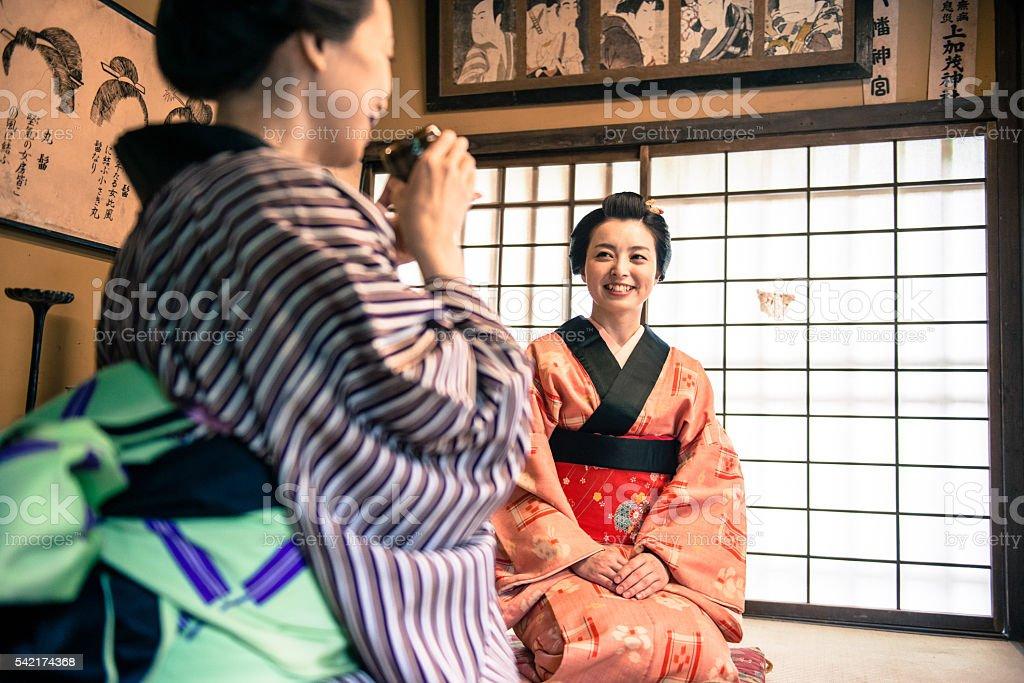 Beautiful smiling japanese women in kimono having matcha green tea at...