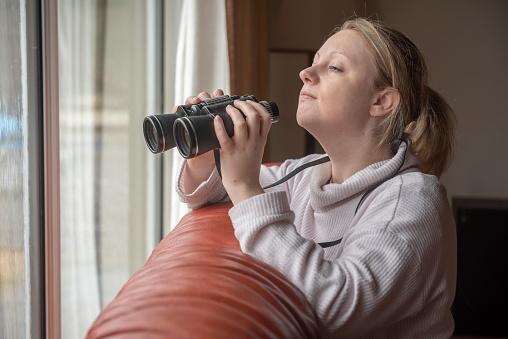 Women in late twenties spying with binoculars through a window