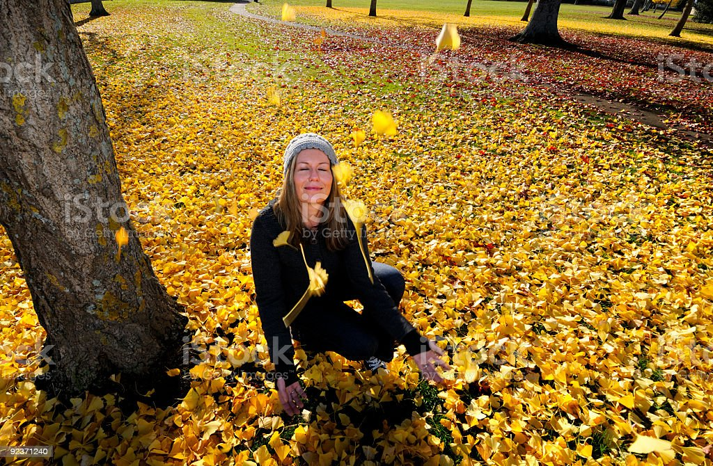 women in park throwing autume leaves royalty-free stock photo