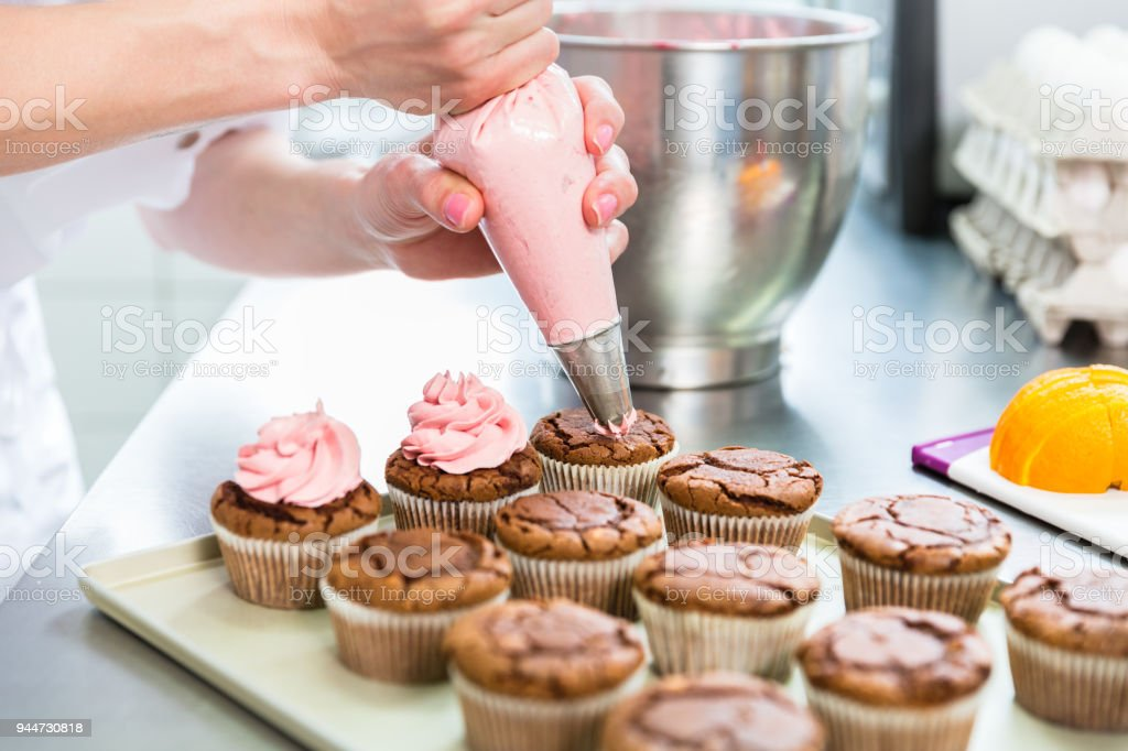 Women in pastry bakery as confectioner glazing muffins with icing bag stock photo